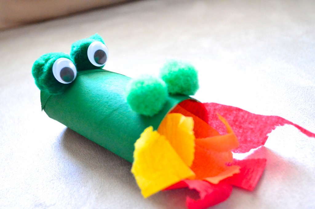 """Pinte su tubo de papel higiénico verde. Si usted es un maestro considerado acerca de los gérmenes, simplemente use un tubo de rollo de toalla de papel cortado por la mitad! He usado pintura acrílica, pero con los niños más pequeños es posible que desee pintura lavable. 2. Una vez que la pintura ha secado el pegamento dos poms verdes del pom del uno al lado del otro en un lado del tubo del papel higiénico para los ojos, y dos poms verdes ligeramente más pequeños del pom en el otro extremo del tubo del papel higiénico para las fosas nasales. 3. A continuación, utilizando puntos de pegamento o pegamento caliente añadir sus ojos googly en un conjunto de poms de pom verde. 4. Una vez que todo se ha secado, simplemente llene sus serpentinas rojas, amarillas y anaranjadas o papel de seda en la """"boca"""" del dragón. Si quieres soplar en el dragón y hacer que las """"llamas"""" revolotean alrededor asegúrese de cinta de las serpentinas dentro del tubo de papel higiénico!"""