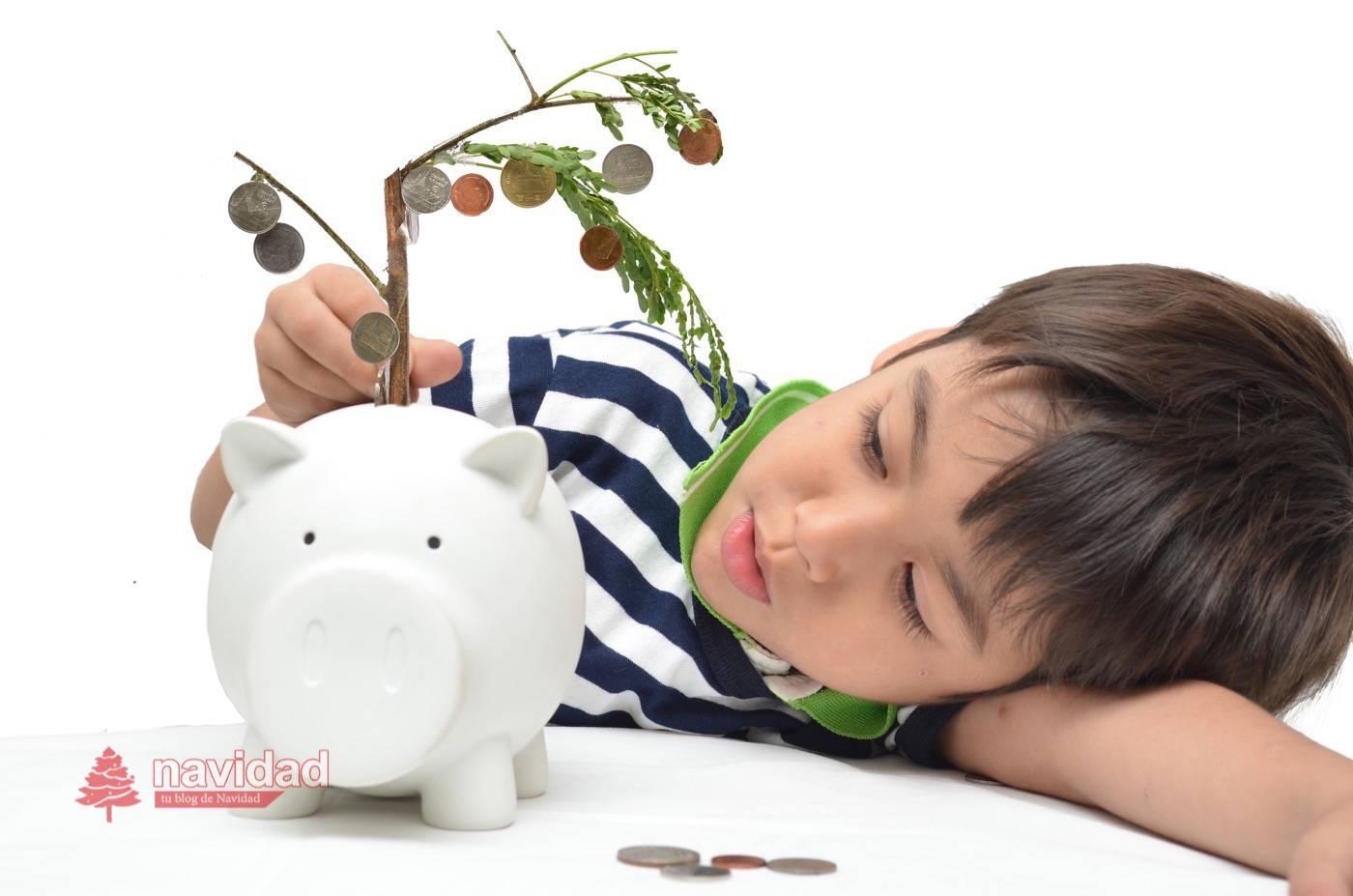 Pequeño niño ahorra su dinero en su hucha cerdito y ve crecer sus ahorros